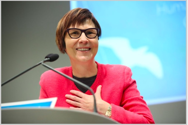 Photo of Dr. Cindy Blackstock delivering speech after receiving the Law Society's Human Rights Award in March 2017. She is at a podium with a microphone. She is smiling and her hand is on her chest.